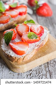 Two toasts or bruschetta with strawberry and mint on cream-cheese on wooden board on table background. Close-up
