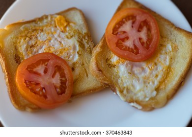 Two toasts with eggs and tomato, selective focus