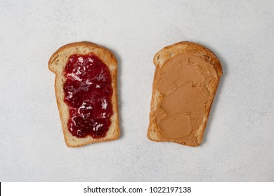 two toasts with peanut butter and jam on a light gray concrete background. view from above