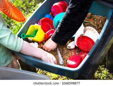 Two toddler arms and hands playing with plastic toys in a tub with sand in it.