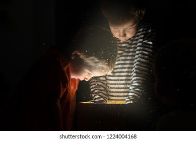 Two toddler boys standing over golden gift box with magical lights and glitters coming out reaching inside for a surprise.