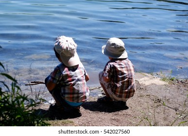 Two toddler boys taken from behind sitting by the lake pretending to be the fishermen and catch the fish with wood sticks
