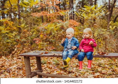 Two toddler children, boy and girl sitting and eating