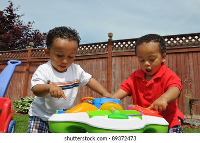 Two Toddlers Playing Outside Looking Down Pointing at Toy