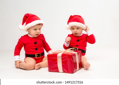 two toddlers in Santa Claus costumes with gift box on white isolate background
