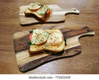Two tomato cheese toasts with parsley on unique shape wooden boards.