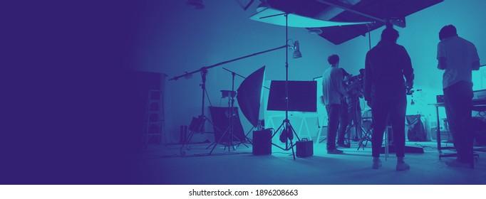 Zwei Töne von hinter der Szene der Fotoproduktion im großen Studio eingerichtet. Professionelles Team arbeitet und Kameraausrüstung in Silhouette. Und Kopienraum hinzugefügt.