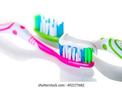 two toothbrushes closeup on against white background