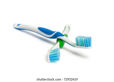 Two toothbrushes. Focus is pointed at the blue bristle brush