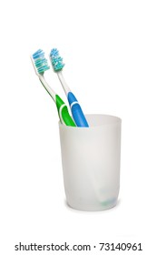Two toothbrushes in glass.  Focus is pointed at the bristle brushes
