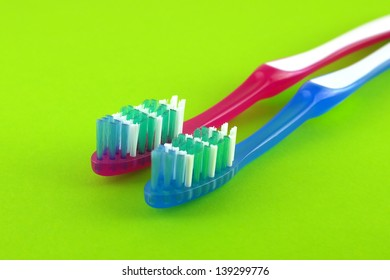 Two tooth-brushes over bright green