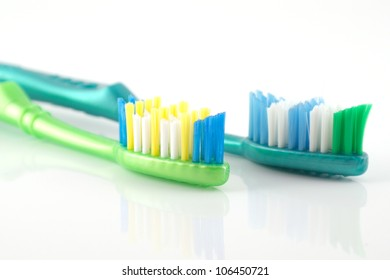 Two tooth-brushes over white