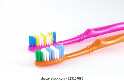 Two tooth-brushes over white, shallow DOF