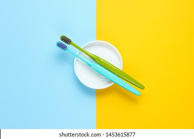 Two toothbrushes, tooth powder on yellow blue background. Minimalism oral hygiene concept. Top view