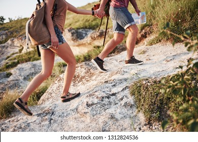 Two tourist with backpacks climb to the top of the mountain and enjoying sunrise.