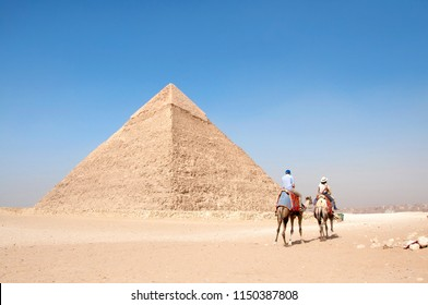 Two tourist camels from the back riding through the desert towards Big pyramids, Great Pyramid of Khufu (Cheops) and Pyramid of Khafre (Chephren) on the sunny day and clear blue sky, Giza, Cairo, Egyp