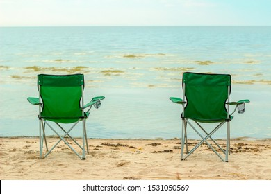 Two tourist chairs stand on the shore against the sea horizon. Back view. concept of meditation and calm and relationships