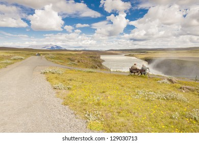 Two tourist on the wooden bench in background Gullfoss waterfall - Iceland.