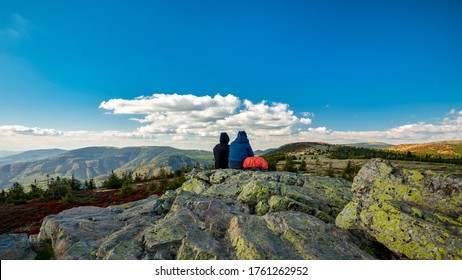 Two tourist sitting on a rock and watching colorful treeless mountain landscape, Jeseniky, Czech Republic.