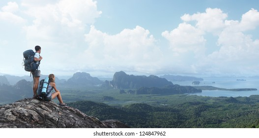 Two tourists with backpacks relaxing on top of a mountain and enjoying valley view