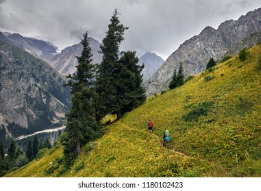 Two tourists with backpacks walking on the trail in the mountain valley at overcast sky background. Travel adventure concept