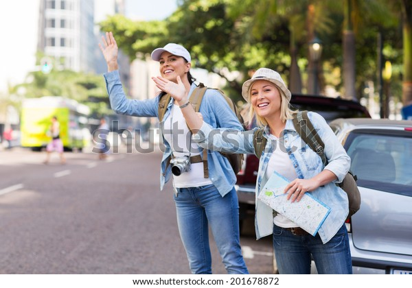 two tourists calling for a taxi in the city
