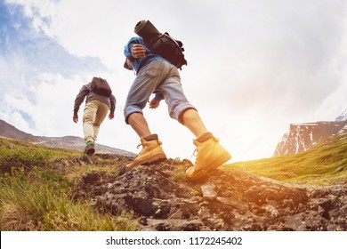 Two tourists are going up at sunset time in mountains area. Trekking or expedition concept