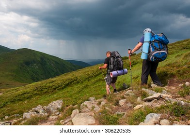 Two tourists with large backpacks on the mountain while a thunderstorm approaches.