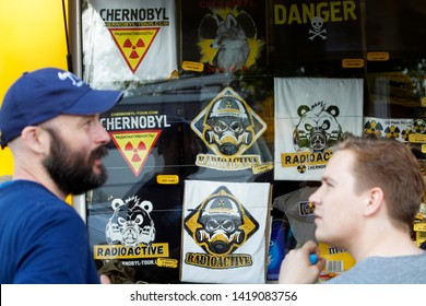 Two tourists look on t-shirts in a Chernobyl souvenir shop in Chernobyl exclusion zone in Ukraine, on June 7, 2019.