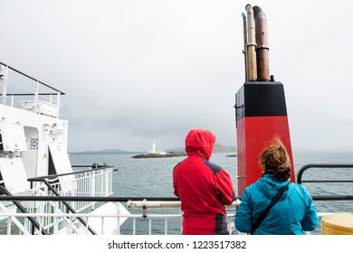 Two tourists looks at the Lighthouse of Lismore during a ferry crossing in the inner Hebrides