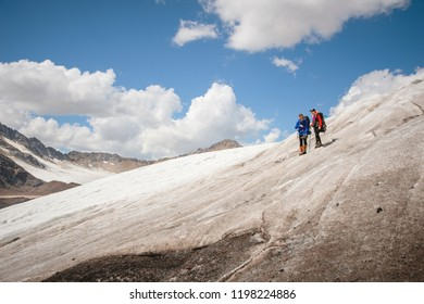 Two tourists, a man and a woman with backpacks and cats on their feet, stand on the ice in the background of the mountains of the sky and clouds. communication in the mountains