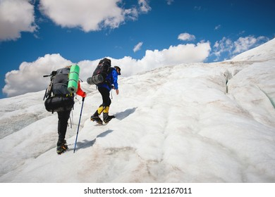 Two tourists, a man and a woman with backpacks and crampons on their feet walk along the glacier against the background of the mountain Elbrus and the sky and clouds. Back view