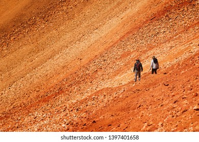 two tourists on steep volcanic slope of Tunupa volcano in Bolivia