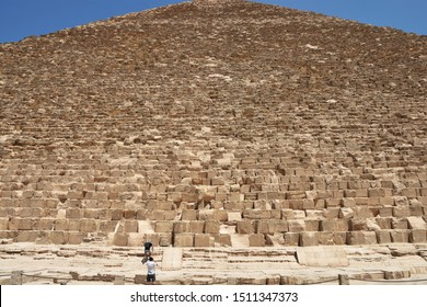 two tourists preparing to make photo at Western side of Pyramid of Khufu or the Pyramid of Cheop, the oldest and largest of the three pyramids in the Giza pyramid complex