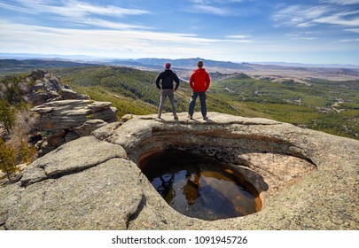 Two tourists standing near small lake and looking on the panorama of beautiful valley Karkaraly national park in Central Kazakhstan