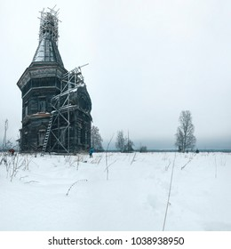 Two tourists visiting the restored wooden church in the wasteland, Russia