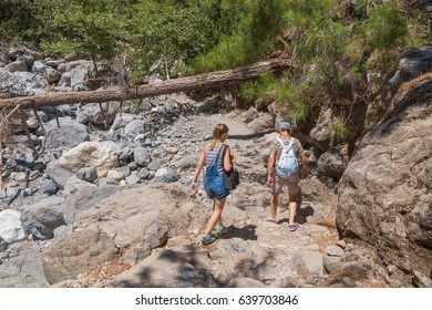 Two tourists, a young girl and a man walking along the trail in the Samaria gorge on the island of Crete, Greece. Active rest in the Samaria national park.