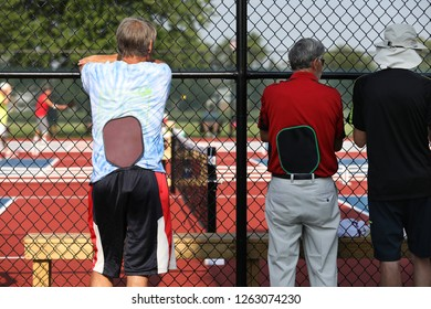 Two tournament players watch as they wait to play in their pickleball match