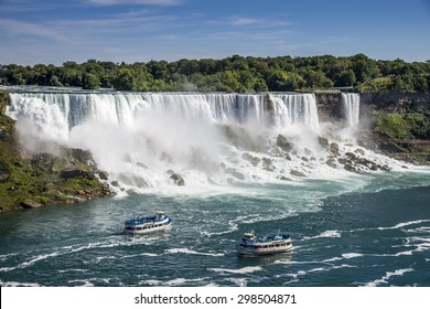 Two tours boats on the Niagara River pass in front of the American Falls in Niagara Falls New York. The photo was taken from Niagara Falls Ontario Canada.