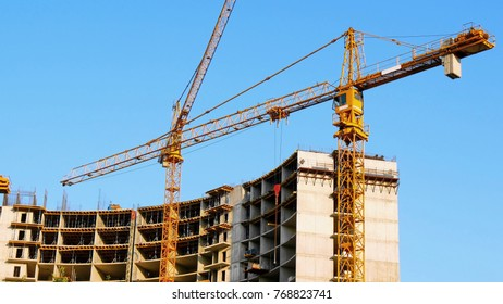 Two tower cranes near building. Construction site. Building under construction.