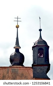Two towers are on the end of a roof. One has a golden orb and double cross. The other is a bell tower. The roof is covered with terracotta tiles. The sky is blue with white  clouds.
