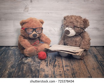 Two toy bears reading and crochet. As an old grandma and grandpa. The concept of old age, family old couple together