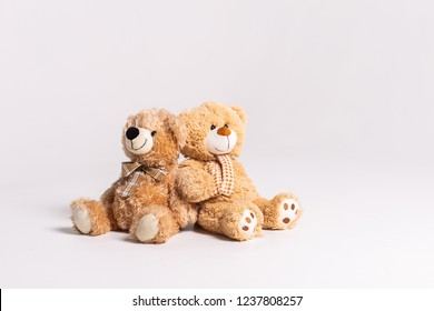 Two toy bears sitting on a white background