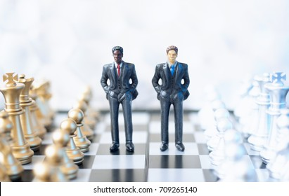 Two toy businessmen, lawyers or politicians on a chessboard.