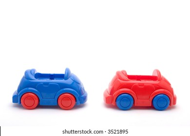 two toy cars, one red, one blue, lined as in a cue, isolated on white