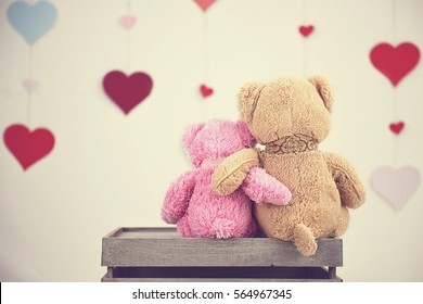Two toy teddy bears sitting in front of hearts