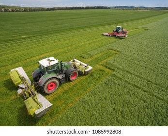 two tractor mowing a green fresh grass field,   farmer in a modern tractors mowing a green fresh grass field on a sunny day - aerial view