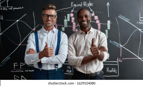 Two traders smiling at camera while standing near wall with charts. Concept of market analysis and business education. Front view