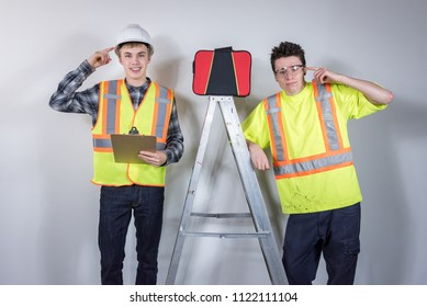 Two tradesmen standing next to a ladder with a safety kit.