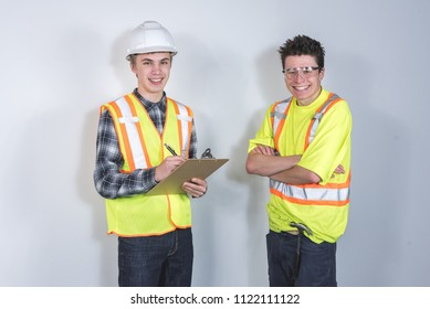 Two tradesmen standing together discussing building plans.